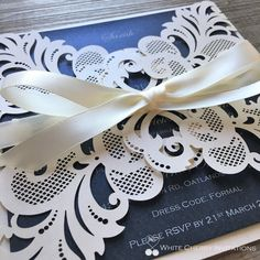 Laser cut wedding invitation by White Cherry Invitations layered with navy metallic card stock and tied off with an ivory satin ribbon. Accompanied with a metallic ivory 160mm x 160mm envelope.