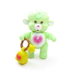 This vintage Care Bears toy is Gentle Heart Lamb, she's one of the Care Bears Cousins. She's light green with a pink heart on her tummy. She has brown eyes and a tuft of green hair on top of her head.