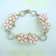 """A great vintage Coro bracelet, with pretty pink flowers in a goldtone setting with rhinestone centers and an additional stone on the side of each of the three components. The bracelet is 7-1/8"""" long,"""
