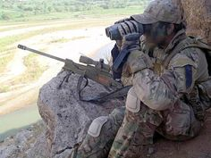 sniper surveys the terrain during a task in Southern Afganistan.
