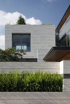 Facade with grass in Travertine Dream House by Wallflower Architecture + Design