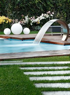 Bring a peaceful vibe into your backyard with a pool fountain or waterfall. -Photo by Kadir Asnaz Photography