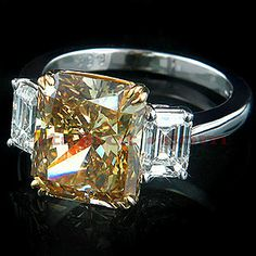 This absolutely luxurious 6.38-carat Deep Brown Diamond Engagement Ring features a Radiant Cut center diamond and 2 dazzling emerald cut side diamonds totaling 1.50 ctw. The center 6.38-carat Fancy Deep Brown Yellow, VS1 clarity Radiant Cut Diamond is accompanied by a GIA report. Set in a handmade platinum and 18K gold frame