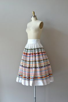 Vintage 1950s white cotton circle skirt heavily adorned with festive and colorful rick rack & decorative ribbon, a high and wide banded waist…