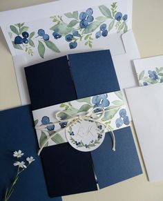 This invitation is printed on white stock, mounted on a navy blue gate fold card. The invitation is closed with a blueberry watercolor belly band tied