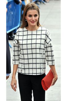 We love how the woven pattern of the queen's clutch echoes the print on her architectural blouse