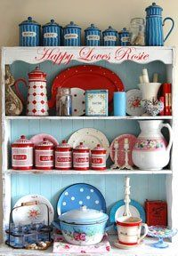 white hutch with blue background and red and blue dishes, teapots, pitchers