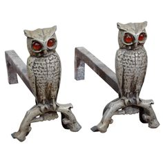 1930's Cast Iron Owl Form Andirons with Amber Glass Eyes  USA  c. 1930  Owl andirons from the 1930's. Complete with amber glass eyes, each owl figure is perched on a branch.
