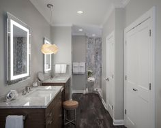Gray stone countertops top double wood vanities in a spacious modern master bathroom. Gorgeous stone tiled floors and a modern pendant lamp are subtle and elegant touches in the open space.