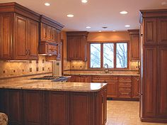 Red birch kitchen cabinets in combination with light-colored granite countertops, tile backsplash and floor
