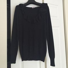 Black J.Crew Merino Wool Sweater Worn a few times but the fabric is in great condition. Lightweight merino wool with ruffle and rosette detail around the neckline. About 24 inches long, measured from highest point in back. Sleeves are about 25 inches, measured from shoulder seam. Fits true to size. J. Crew Sweaters