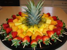Obstspieße für eine Party – In der Mitte thront das Blattwerk einer Ananas, um… Fruit skewers for a party – In the middle, the foliage of a pineapple sits enthroned to stabilize the skewers.