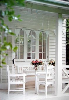 Pretty white porch, twinkle lights, garland, table, chairs and flowers for color.