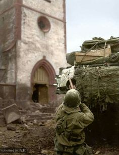 An American soldier from Company B, 68th Armored Infantry Battalion, 4th Armored Division, engages German snipers entrenched in a spire of the church of Saint-Michel, while the tank in the foreground provides supporting fire in Place de l'Église, Oberhoffen-sur-Moder, Bas-Rhin, Alsace, France. February 6 1945.  (The church was destroyed during the liberation of the town and was rebuilt in 1956)