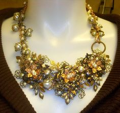 From B'sue of B'sue Boutiques, assemblage work with brass stampings, vintage costume pearls and caged pearls.