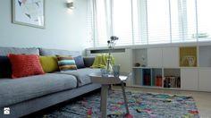 szara sofa z kolorowymi poduszkami i białe meble w salonie