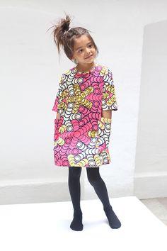 KWADUSA - SUKIENKA PINK RINGS - Ta niezwykle szykowna sukienka sprawdzi się na różne okazje. Jest obszerna i rozszerzana ku dołowi, ma szerokie proste rękawy do łokcia, 2 duże naszywane kieszenie po bokach, pionowe przeszycie na plecach zakończone na górze krótkim różowym suwakiem. Wibrujące kolory zdradzają pochodzenie sukienki – sukienkę uszyto w Kenii (w warsztacie przestrzegającym praw pracowniczych).