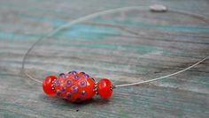 Oliva+s+fialovýma+bublinkama+na+ocelovém+lanku+Jasně+červená+vinutka+ve+tvaru+olivy+s+fialovýma+bublinkama+na+ocelovém+lanku+doplněnázkaždé+strany+rondelkou.Délka+lanka+je+45+cm.Velikost+olivy+je+28+x19,5+mm,rondelky+8x12,5mm.