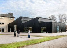 Primus Arkitekter transformed a Fritz Hansen furniture factory into an elegant library and community center in Allerød, Denmark.