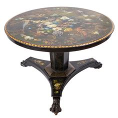 Early Victorian Painted Slate Breakfast Table  Wales  Circa 1840  Early Victorian Slate Tilt Top Table with a hexagonal column above a triform base ending in carved paw feet. The table is entirely veneered in slate, and is decorated with birds of paradise and roses. It has a hexagonal base column with more slate paneling. This table echoes the Regency Style, with early Victorian decorative elements. The table probably originated from Wales, explaining the Regency proportions on an 1840's…