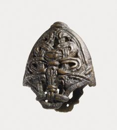 Viking leaded copper alloy chape from a sword scabbard. A a face above a triangle at the centre in typical Borre style, 10thC.