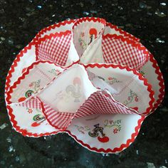 Rooster Gingham Bun Holder, a perfect item to have for that special dinner to place your massa sovada in!   Contents: 100% Cotton, Details: Galo de Barcelos & Gingham print Snaps together to create holder for dinner rolls, folds flat for storage Imported from Barcelos, Portugal  Available for purchase at www.RoosterCamisa.com