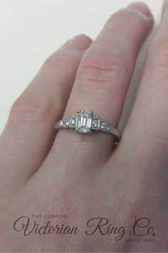 This emerald cut engagement ring in platinum is based on an original Art Deco era design from the early 1930s. The stepped shoulders are a strong Art Deco motif that echo ancient buildings and the more modern city skyscrapers. A round diamond is set in each of the three steps, while every level is millegrain edged with tiny beads of platinum. #diamondengagementring #diamondring #artdecoengagementring #steppedshoulderengagementring #vintagestylering Emerald Cut Diamond Engagement Ring, Emerald Cut Diamonds, Engagement Ring Cuts, Round Diamonds, Ancient Buildings, Vintage Style Rings, Modern City, Art Deco Design, Skyscrapers