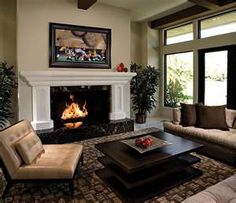 Im loving the tv over the fire place and how the couches and chair surrounds the square coffee table.