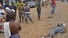 People stand around a man, right, suspected of suffering from the Ebola virus in a main street and busy part in Monrovia, Liberia, Friday, Sept. 12, 2014. The virus continues to rage through West A...