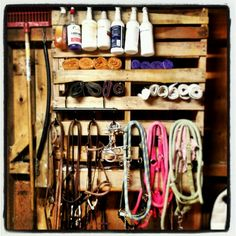 Use a pallet with tightly spaced rails and hang on nails. Great for organizing bridles and wraps and anything hangable