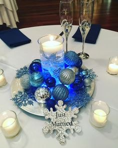 Simple Winter Centerpieces using chargers, ornaments, lights, cylinders with water and floating candles.