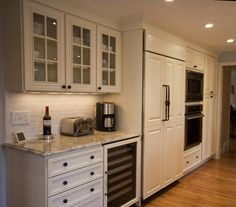 Traditional ivory kitchen with island, built in refrigerator, wine cooler