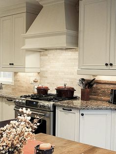 spacious white kitchen with light travertine backsplash and