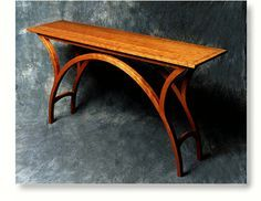 "Arch Table shown in cherry, with black resin inlay The Chicago Tribune described this elegant table as ""firmly in the best tradition of Chicago design."" Winner of the Distinguished Furniture Design Award from the Chicago Athenaeum Museum Height 32"" Width 60"" Depth 15"" Arch Table..... $3295."