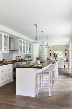 Kitchen Lighting Idea – Kitchen Design Ideas & Images (houseandgarden.co.uk) The dining table is not the only place to sit in designer  Helen Green's open-plan kitchen. Her clever design provides lots of additional spaces including a cosy window seat and simple stools ranged along the central island to ensure that the kitchen is the heart of the house.