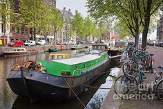 Boats and bikes on Geldersekade canal waterfront in Amsterdam, Holland.