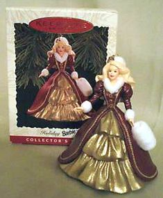1996 Holiday Barbie Ornament  (SHE HAS THIS ONE)    The 1996 Holiday Barbie Ornament was a replica of 1996 Holiday Barbie doll in a fur trimmed gold and burgundy gown. She also has a fur mitt & hat.