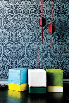 Square bi-colored ceramic stools, teal wallpaper and red.  Stools from Anthropologie.