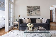 """A dark <a href=""""http://www.westelm.com/products/rochester-sofa-h340/?pkey=csofas%7Call-sofas"""" target=""""_blank"""">sofa</a> was used as a base for the otherwise white room. Marble-like abstract art adds depth to the space, and the glass <a href=""""http://www.overstock.com/Home-Garden/Course-Clear-Glass-Coffee-Table/8533900/product.html"""" target=""""_blank"""">waterfall table</a> provides a great surface area without taking up any visual space."""