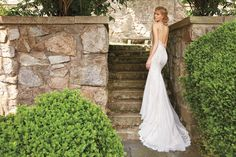 Ivory French Corded lace over Champagne Charmeuse slim bridal gown with shimmer throughout. Jeweled embroidery throughout the bodice and flowing into the skirt. Curved sweetheart neckline with beaded spaghetti straps and open back with skirt godets.
