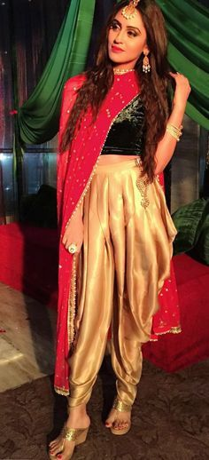 Krystle D'Souza sported the perfect amount of edginess while attending an Arabian-themed sangeet/mehendi night of her friend. She opted for gold dhoti pants by Sandhya Shah, and paired it up with a black velvet crop top and a fuchsia pink dupatta.