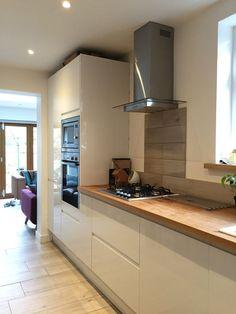 Howdens white gloss intergrated kitchen with solid oak full stave worktops .. Wood effect porcelain tiles splashback and neff slide n hide oven
