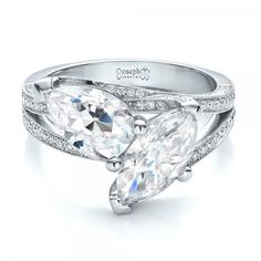 #100392 This dazzling engagement ring features a pear shaped diamond and marquise shaped diamond, both prong set atop a criss-cross split shank, with bright cut set diamonds...