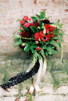 Brides.com: . A red bouquet comprised of garden roses, anemones, berries, and greenery, created by Sweet Marie Designs.