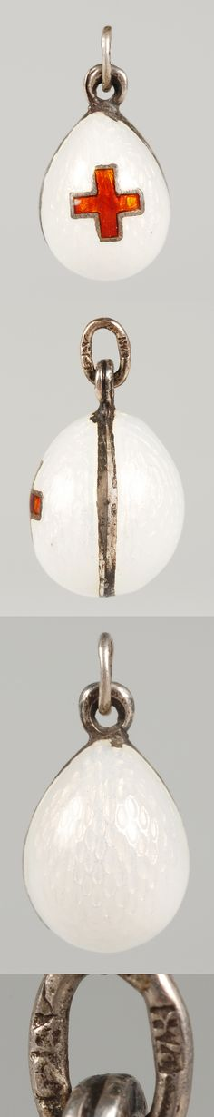 "A Faberge silver and guilloche enamel pendant egg, workmaster Feodor Afanasiev, ST Petersburg, circa 1900. The body flooded with white enamel over a wavy engine turned ground centering a red enamel cross. Height: 1/2"" (1.3 cm)."