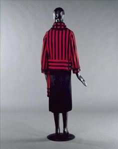 Jacket (back view)   Jean Patou   France, 1922   Red and black wool cloth   Patou's comfortable jersey sportswear ensembles, golf and tennis attire and swimsuits did much to establish the reputation of his boutique, Le Coin des Sports. A notable feature of this jacket is the cut and the skilled criss-crossing of the black ribbon on the collar, wrists and waist   Palais Galliera, musée de la Mode de la Ville de Paris