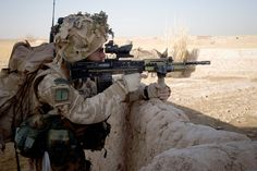 A Royal Marine with 42 Commando takes aim with a SA80A2 rifle while on an operation in Helmand Province, Afghanistan, 2008. Note the Trijicon Advanced Combat Optical Gunsight (ACOG) TA31RCO 4 x 32 sight. An additional CQB red dot sight is mounted atop the ACOG for short range engagements.