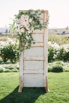 A stunning vintage door used at the altar, adorned with a custom garden arrangement. Floral design by The Flower House.