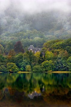 Loch Achray, Scotland with a low mist slowly drifting along the hillside behind this lovely cottage.