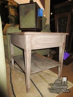 """Distressed end table in a greige color with a shelf below. Great find for a coastal or shabby chic style home! Measures 26""""long x 20""""deep x 22""""high."""